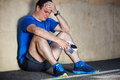 Upset young male runner resting leaning against wall Royalty Free Stock Photography