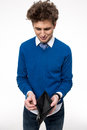 Upset young man holding emty wallet over white background Royalty Free Stock Photo