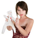 Upset young white woman sticking pin in doll Royalty Free Stock Photos