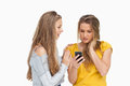Upset young woman holding her cellphone consolded by her friend Stock Photo
