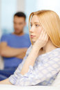 Upset young woman with man on the back at home Royalty Free Stock Photo