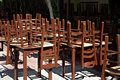 Upside down closed restaurant with old fashioned brown wooden chairs set on tables at sunny summer day Stock Photo