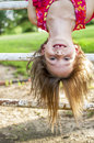 Upside down happiness girl hanging on an old gate she is missing her front teeth Royalty Free Stock Photo