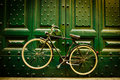 Urban bicycle classic bike hanging on a big green door Royalty Free Stock Image
