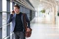 Urban business man talking on smart phone traveling walking inside in airport casual young businessman wearing suit jacket and Stock Image