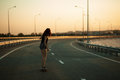 Urban fashionable girl riding longboard outdoors on the road at sunset. Royalty Free Stock Photo