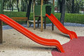 Urban furniture for children amusement park red plastic toboggans with green wooden houses Royalty Free Stock Images