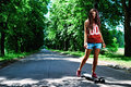 Urban girl with longboard outdoors in summer Stock Photo