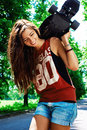 Urban girl with longboard outdoors in summer Stock Photos