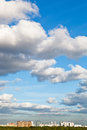 Urban houses under big white clouds in blue sky spring Stock Photo