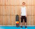 Urban man sunglasses and skateboard posing on wood planks background. Good looking. Cool guy. Wearing white shirt and black pants. Royalty Free Stock Photo