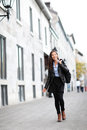 Urban modern woman walking in city street outdoor female fashion model wearing cool leather jacket and shoes outside happy ethnic Royalty Free Stock Photography