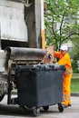 Urban recycling waste and garbage services worker of collector truck loading trash bin Stock Images