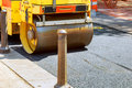 Urban road is under construction, asphalting of yellow roller Royalty Free Stock Photo