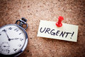 Urgent written on a post note and hanged on the cork board with an old pocket watch Royalty Free Stock Photography