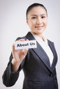 About us business woman with a paper card with on it Royalty Free Stock Image