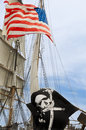 Us flag and black flag on bark barkl decked out with of the usa a jolly roger Royalty Free Stock Photography