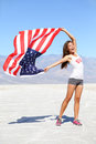 Us flag woman athlete showing american flag usa sport winner cheering waving stars and stripes outdoors in desert nature Royalty Free Stock Photos