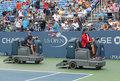 US Open cleaning crew drying tennis court after rain delay at Louis Armstrong Stadium at Billie Jean King National Tennis Center Royalty Free Stock Photo