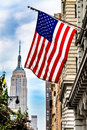 Usa lage and empire state building a photograph of the united states flag with the in the background Stock Photography