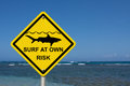 Use caution when surfing because sharks are present an warning sign at the beach with shark symbol and words surf at own risk Stock Photos