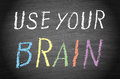 Use your brain text in uppercase letters written on a black chalkboard with in multicolored letters and in white Royalty Free Stock Photos
