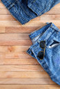 Used Jeans and Aviator sunglasses on top of wooden Royalty Free Stock Photo