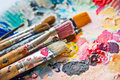 Used paint brushes on a colorful palette Royalty Free Stock Photo