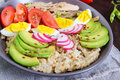 Useful breakfast: oatmeal with rabbit meat, avocado, boiled egg, tomatoes, radish Royalty Free Stock Photo