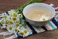 Useful herbal tea with chamomile in a white cup daisy flowers on a hand woven rug Royalty Free Stock Photos