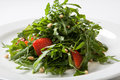 Useful strawberry salad with arugula nuts and honey on the white plate