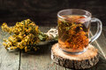 Useful tea with dried st john s wort freshly brewed in a glass mug on a wooden table selective focus Stock Images