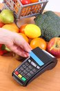 Payment terminal with contactless credit card and fresh fruits and vegetables, cashless paying for shopping Royalty Free Stock Photo