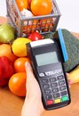 Payment terminal with credit card and fresh fruits and vegetables, cashless paying for shopping Royalty Free Stock Photo