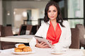 Using ipad attractive woman looking at camera while sitting at restaurant Royalty Free Stock Photography