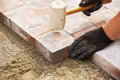 Using a mallet to set paver installing bricks on patio level the stones Royalty Free Stock Photos
