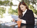 Using tablet young woman computer in coffee shop Stock Image