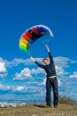 Using wind energy man standing on a hill with a kite and feeling the power Stock Photos