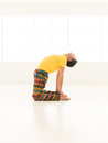 Ustrasana pose colorful dressed male repeating yoga exercises in a white room with window background Stock Photo