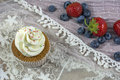 Usual vanilla cupcake with white cream with many strawberries and blueberries Royalty Free Stock Photo