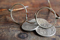 Usury concept three ancient russian silver coins near spectacles on wooden background Stock Images