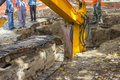 Utility crew works excavator arm digging deep hole seeking cracked sewage pipe Royalty Free Stock Image