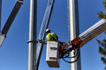 Utility worker in boom crane basket workers a servicing poles Stock Image