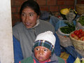Uyuni bolivia september uyuni bolivia children with his mother at the fruit market Royalty Free Stock Photo