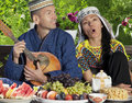 Uzbekistan couple playing mandolin dressed in clothes and singing during breakfast Stock Image