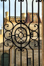 Uzes france village in the south of duke s palace on sundown viewed through ornate forged fence Stock Photography