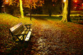 Vacant park bench in autumn photo of a at night Stock Photography