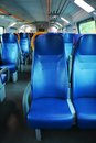 Vacant seats inside an italian modern train blue and windows a names and logos removed only general warning signs remain Stock Photography