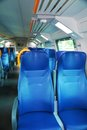 Vacant seats inside an italian train blue a modern names and logos removed only general warning signs remain Royalty Free Stock Image