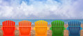 Vacation beach chairs on sand a rainbow of colors of wooden are lined up along the water shore there is copyspace in the clouds Stock Photos